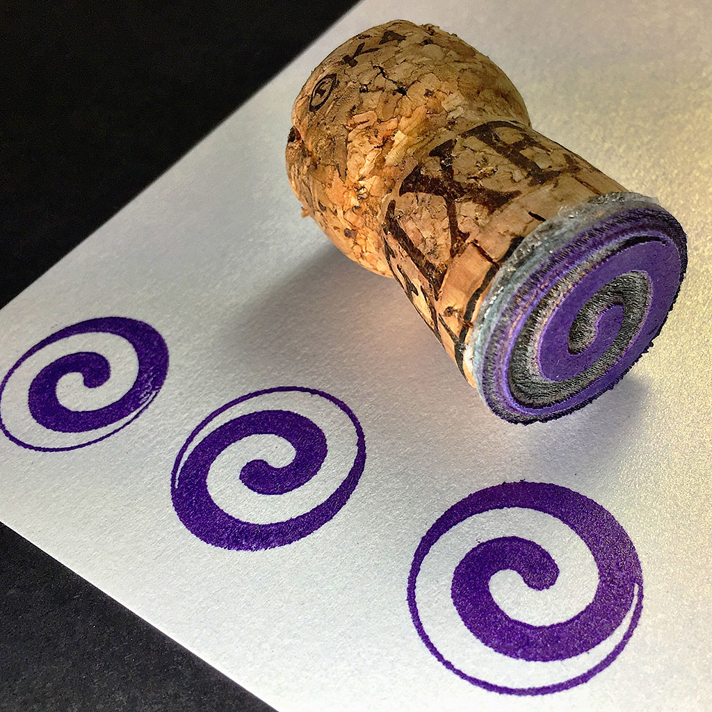 Lasercut spiral stamp mounted on champagne cork