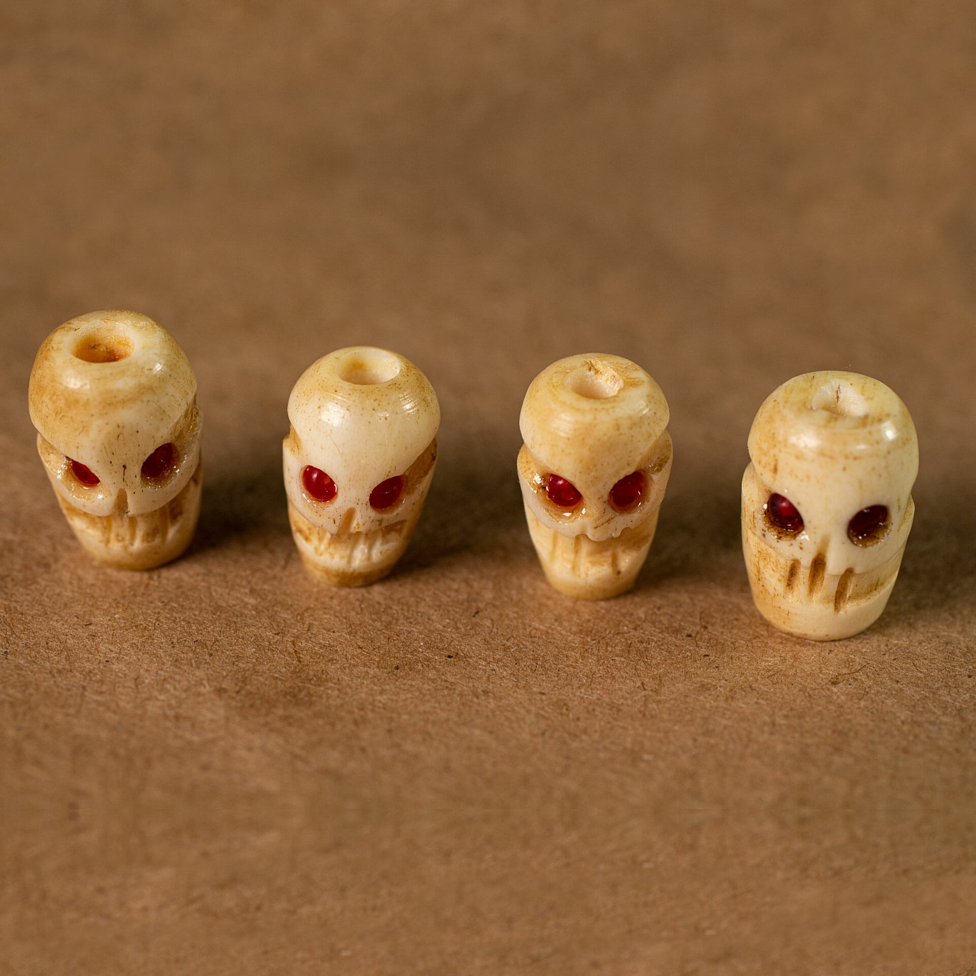 Cow bone skull beads with red seed bead eyes